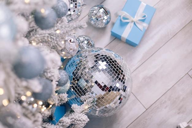 크리스마스 트리 아래에 디스코 공과 선물이 놓여 있다
