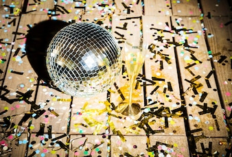 Disco ball and glass of drink between confetti