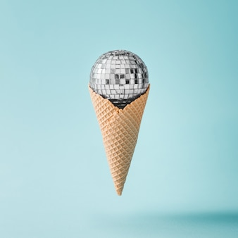Disco ball ice cream on bright blue surface