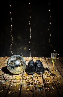 Disco ball, man's boots and glass of drink between confetti