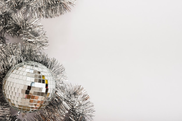 Disco ball with tinsel on white table