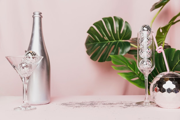 Disco balls in champagne glasses and monstera plant