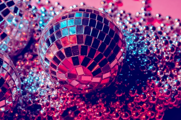 Disco balls for decoration of a party on pink background