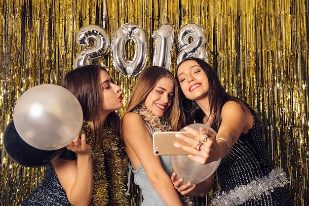 Ragazze di discoteca che prendono selfie sul partito di nuovo anno