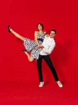 디스코. 빨간 스튜디오 배경에서 격리된 구식 젊은 부부 춤. 아티스트 패션, 모션 및 액션 컨셉, 청소년 문화, 패션 복귀. 세련 된 젊은 남자와 여자.