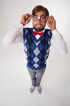 Disconcerted geek man correcting eyeglasses isolated