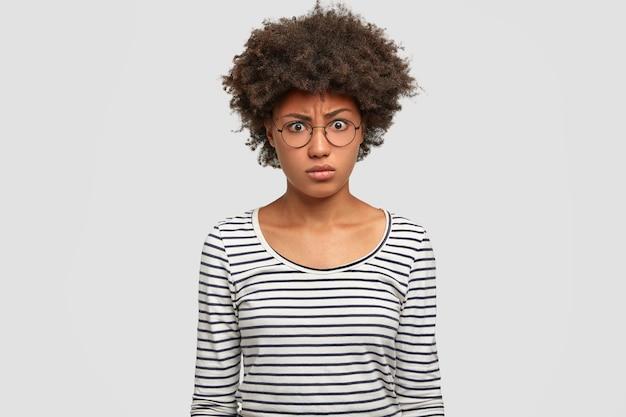 У недовольной афроамериканки кудрявые темные волосы
