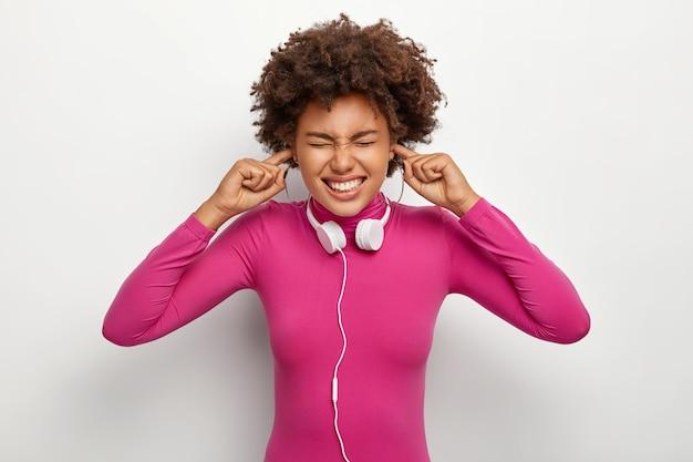 Недовольная афро-женщина с вьющимися волосами, затыкает пальцы в ушных отверстиях, игнорирует неприятный громкий шум