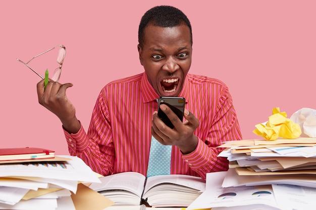 Il malcontento uomo di colore infastidito fissa lo schermo del moderno telefono cellulare, riceve cattive notizie sul messaggio, tiene gli occhiali
