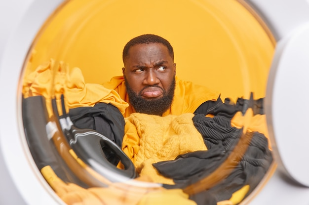 Discontent bearded man looks unhappily away smirks face sticks through laundry with liquid powder looks away poses from inside of washig machine in laundromat