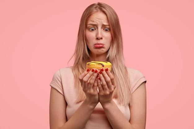 不満の金髪の女性は甘いドーナツを持って、誘惑に見え、食べたいが、ピンクの壁に隔離されたカジュアルなtシャツを着てダイエットを続けています。人とジャンクフードのコンセプト。