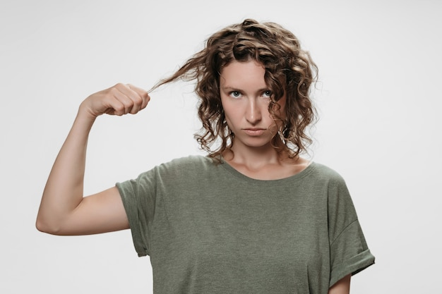 Discontent curly brunette woman, frowns face with displeasure