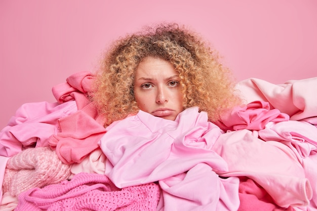 Discontent curly haired woman looks sadly at camera
