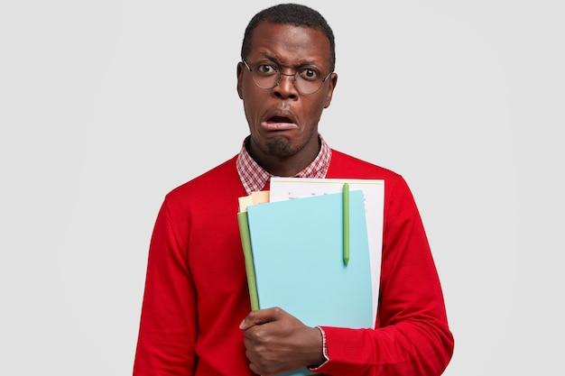 Недовольство темнокожий мужчина недовольно хмурится, несет бумаги, носит повседневную одежду, недовольно смотрит