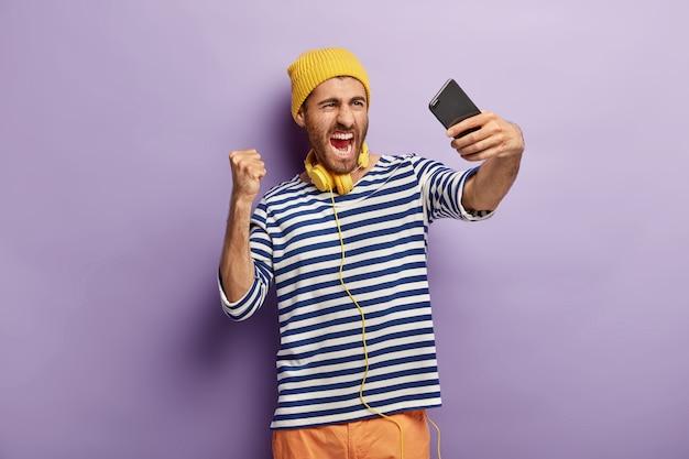 불만의 감정적 인 화난 남자가 셀카 사진을 찍고 카메라에 부정적인 감정을 표현하고 주먹을 움켜 쥐고 노란 모자와 줄무늬 점퍼를 입습니다.