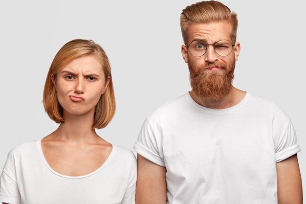 不満のある女性と男性の同僚は、唇と眉をひそめた顔を財布に入れ、財政状況を改善する計画を嫌い、カジュアルなtシャツを着て、隣同士に立ち、白い壁に隔離されています