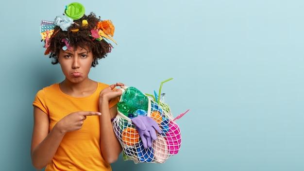 Modello femminile scontento con la pelle nera, raccoglie la spazzatura, indica i rifiuti di plastica con dispiacere, fa volontariato, protegge l'ambiente, si trova su un muro blu con spazio libero per il tuo testo