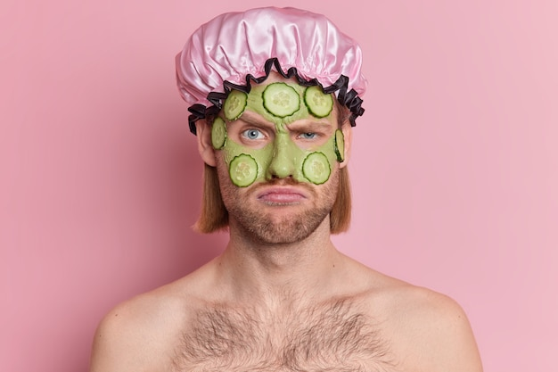 Discontent man frowns face looks unhappily applies green facial mask with cucumber slices wants to have healthy skin wears bath hat stands shirtless.