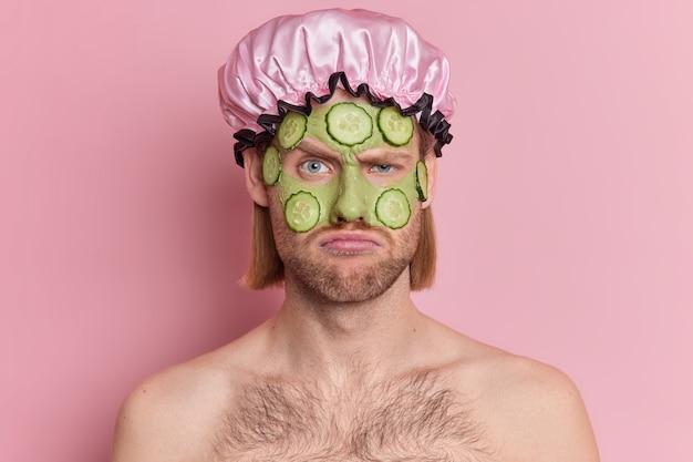 不満の男は顔を眉をひそめているように見えます不幸にもキュウリのスライスで緑の顔のマスクを適用します健康な肌を着てもらいたいバスハットは上半身裸で立っています。