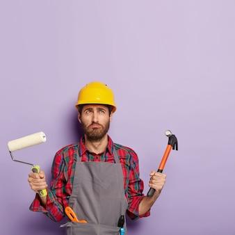 불만족스러운 남자는 보호용 안전모, 앞치마를 착용하고 페인트 롤러와 망치를 들고 집 수리로 바쁘고 노동 도구를 들고 있습니다.
