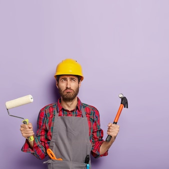 Discontent man wears protective hardhat, apron, holds painting roller and hammer, busy with house renovation, holds labor tools