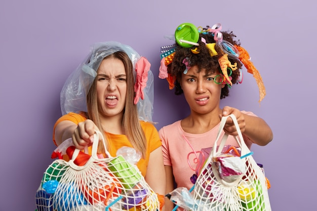 Discontent mixed race women show garbage bags with apathy, feel dislike, fight against ecological problem, collect plastic rubbish, isolated over purpe wall. good friends do volunteering work