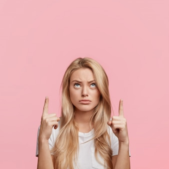 Discontent pretty blonde woman points with fore fingers above head at blank copy space, looks in bewilderment upwards as demonstrates something strange, isolated over pink wall