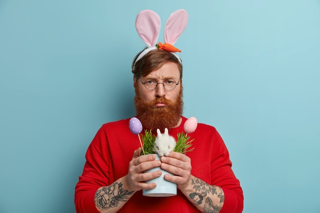 Discontent red haired man smirks face and looks unhappily, has spoiled day, poses with small easter bunny, decorated colorful eggs, wears round spectacles, rabbit ears, poses with gloomy expression