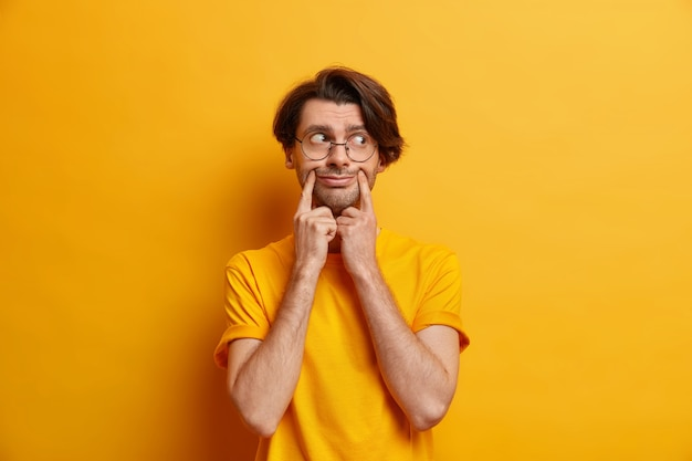 Discontent unshaven european man forces smile keeps index fingers near corners of lips wears round eyeglasses casual t shirt isolated over yellow wall. hipster guy pretends being happy