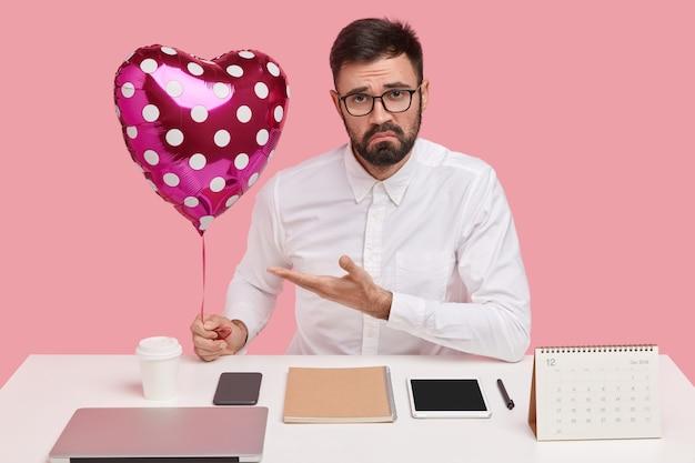 Il malcontento uomo con la barba lunga dimostra san valentino o palloncino, ha un'espressione infelice, indossa occhiali e maglietta, essendo perfezionista