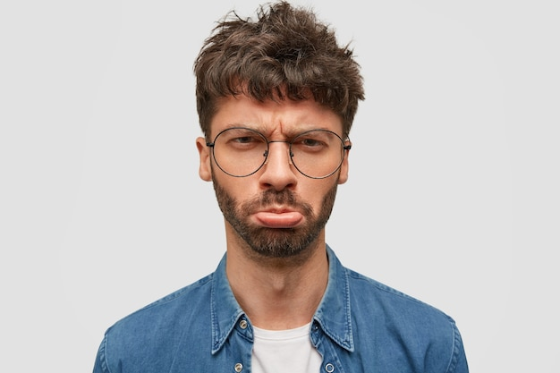 Discontent unshaven young man purses lips and has miserable expression, being grieved