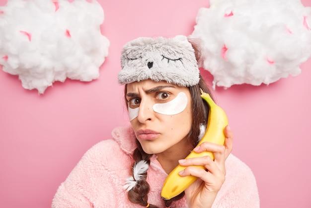 不満の女性は怒ってカメラを見て目の下にコラーゲンパッチを適用し、電話としてバナナを保持します