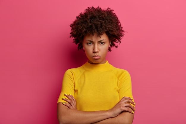 찡그린 표정으로 불만을 품은 여성은 팔을 접은 채로 화를 내고, 나쁜 말을 듣고 화를 내고, 불쾌한 표정을 짓고, 밝은 노란색 옷을 입고 분홍색 벽에 고립 된