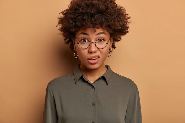 La giovane donna afroamericana insoddisfatta esprime disprezzo e incredulità, sorride con insoddisfazione, indossa occhiali da vista e camicia trasparenti, posa in interni contro il muro marrone