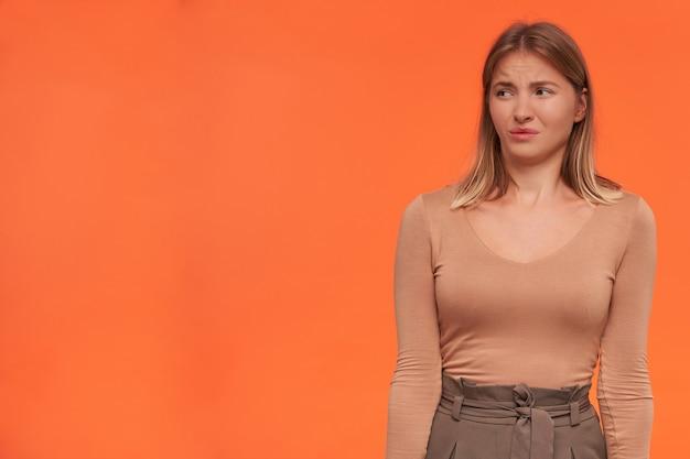 Malcontento giovane attraente donna bionda dai capelli corti con acconciatura casual che fa smorfie il viso mentre guarda da parte, tenendo le mani lungo il corpo mentre posa sopra la parete arancione
