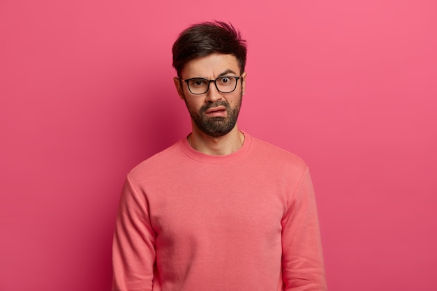 Discontent young bearded man has disgusted displeased expression, reacts on something unpleasant, frowns face, wears spectacles and jumper, stands indoor against pink wall. emotions concept