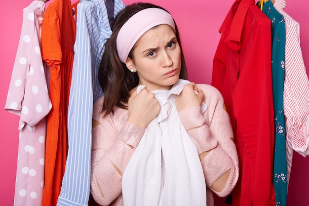 Discontent young female embraces white blouse. beautiful woman wears rose sweater and hair band. upset girl with lots clothes in wardrobe. charming lady isolated over pink wall fashion concept.