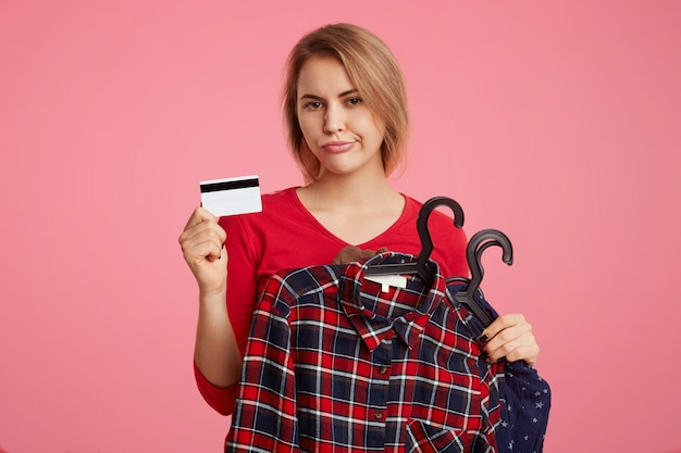Discontent young female model poses with clothes and plastic card, makes shopping online, has no money for buying new purchase