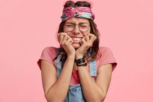Discontent young hippie female has negative facial expression, bites finger nails in depression, dressed in casual clothes and headband, closes eyes with sadness, isolated over pink wall.