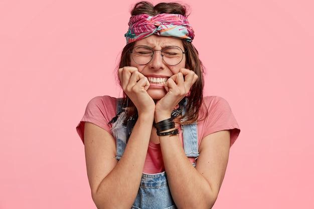 不満の若いヒッピーの女性は、否定的な表情をしており、うつ病で指の爪を噛み、カジュアルな服とヘッドバンドを着て、悲しみで目を閉じ、ピンクの壁に隔離されています。