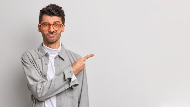 Il giovane scontento esprime avversione e antipatia punta il dito indice da parte sullo spazio della copia deluso dal cattivo prodotto vestito con abiti eleganti isolati sul muro grigio. cosa disgustosa