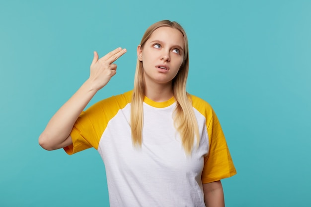 Discontent young pretty fair-haired woman with natural makeup raising hand with weapon gesture to her head and looking upwards with bored face, isolated over blue background