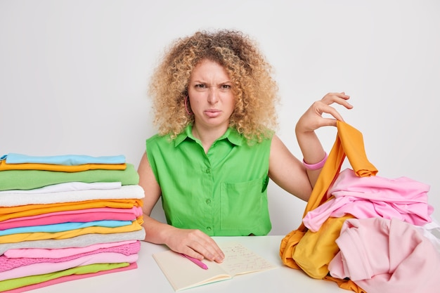 Discontent young woman looks with dislike at untidy laundry writes down information about synthetic wash poses at table folded multicolored clothes near. clothing care and laundering concept