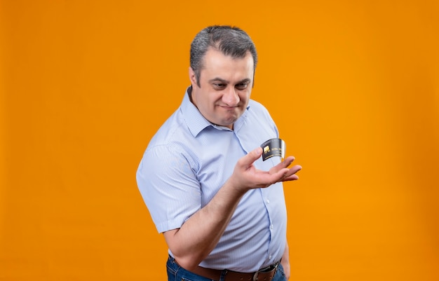 Discontented middle age man in blue striped shirt bending credit card with fingers