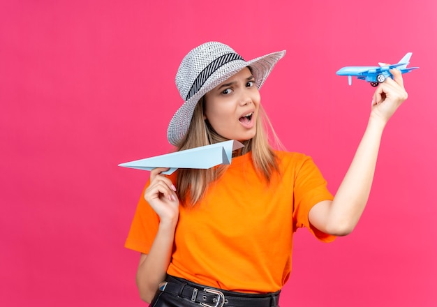 A discontented pretty young woman in an orange t-shirt wearing sunhat flying paper airplane while holding blue toy plane on a pink wall