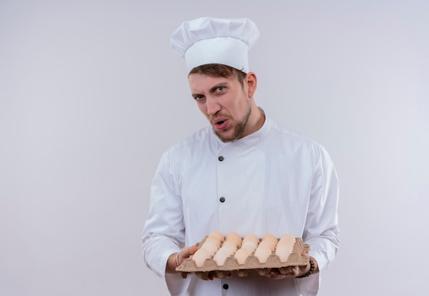 A discontented young bearded chef man wearing white cooker uniform and hat holding a carton of eggs while looking on a white wall