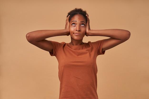 ブロンズのtシャツに身を包んだ不満の若い暗い肌の巻き毛の女性は、耳に手を上げて、ベージュの上に立って、不快な顔で上向きに見ています