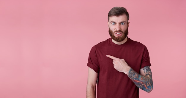 Discontented young handsome red bearded man in red shirt, wants to draw your attention to copy space on the left side, frowns face in displeasure, stands over pink background.