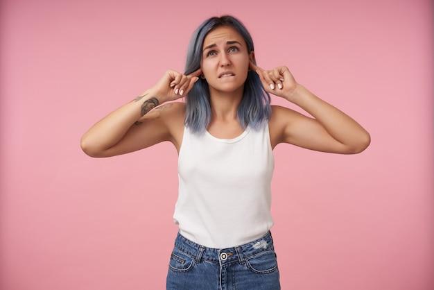 不満を持った若い入れ墨の青い髪の女性が下唇を噛み、迷惑な音を避けながら人差し指を耳に挿入し、ピンクでポーズをとる
