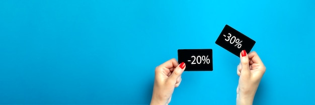 手持ちの割引カード。購入の割引20、30、パーセント。女性は青い背景に黒い割引カードを持っています。広告または印刷用のバナーまたはポスター。テキストの場所